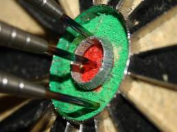 Red dot on the wall; Close of of darts in bullseye