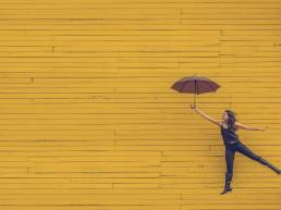 Umbrella in the sun; Lady jumping with umbrella in front of yellow wall